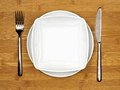 Dining set bowl and plate with fork and knife on a bamboo wood background Royalty Free Stock Photo