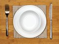 Dining set bowl and plate with fork knife and napkin on a bamboo wood background Royalty Free Stock Photo