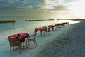 Dinner on the beach five tables and some chairs a tropical at dusk Royalty Free Stock Image