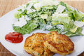Dinner of crab cakes with caesar salad a cocktail sauce Royalty Free Stock Photography