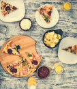 Dinner with pieces of pizza on board and plates Royalty Free Stock Photo