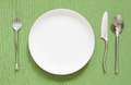 Dinner place setting a white plate with silver fork and spoon Royalty Free Stock Photo