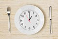 Dinner plate with clock face on wooden table Royalty Free Stock Photo