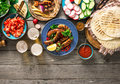 Dinner table with grilled sausage, tortilla, beer and different Royalty Free Stock Photo