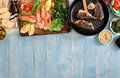 Dinner table with shrimp, fish grilled, salad, snacks with borde Royalty Free Stock Photo