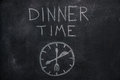 Dinner time text with clock on black chalkboard Royalty Free Stock Photo