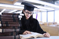 A diploma is reading books at reading room happy student in graduation cap Stock Photography