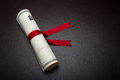 Diploma with a red ribbon on a black leather background Stock Photos