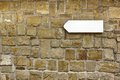 Direction signboard on the old stone wall background and texture for text or image Stock Images