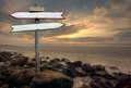 Directional signs double on a beach at sunset Royalty Free Stock Photography