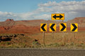 Directional traffic arrows bright yellow arrow signs along desert highway Royalty Free Stock Images
