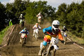 Dirt bike competition motocross riders during amateur on muddy track Royalty Free Stock Image