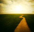 Dirt pathway to the sunset beautiful in a grassy field with a Royalty Free Stock Photo
