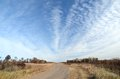Dirt road with altocumulus clouds in the sky Royalty Free Stock Photography