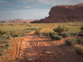 Dirt road in desert a leads through sage brush country to red sand stone cliffs the distance near canyon lands national monument Stock Photos