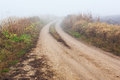 Dirt road in mist cold autumn morning Royalty Free Stock Photography
