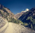 Dirt road through a mountain valley annapurna circuit in nepal Royalty Free Stock Images
