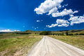 Dirt road mountains summer landscape color photo image on the high in the at midday on a summers day with clear blue sky and cloud Royalty Free Stock Images