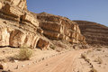 Dirt road in the negev desert a marked with stones follows a line of rocky cliffs through southern portion of israel Stock Photo