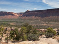 Dirt road up the mountain a goes from desert valley and side of red rock cliff in southern utah Stock Photo