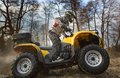 Dirt spinning of the atv quad bike wheels horizontal motion portrait a man in gray sport jacket and safety helmet and goggles Stock Image