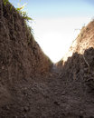Dirt trench inside a irrigation with blue sky Stock Photo