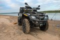 Dirty atv stands on the banks of the river Stock Photos