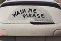 Dirty back window of the car and inscription Wash me please Royalty Free Stock Photo