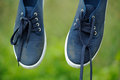 Dirty blue sneakers on clothes line hanging a outdoors Stock Photography