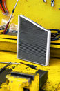 Dirty car air filter removed from a vehicle during a service standing on a yellow bench in the workshop Royalty Free Stock Image