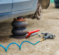 Dirty car pneumatic tools and at a service workshop for a tyre change on old concrete Stock Photography