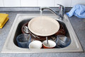 Dirty dishes pile of in kitchen sink with running water Stock Images