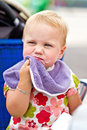 Dirty faced little girl after eating drying her face Stock Photos