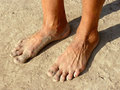 Dirty feet male on dried earth Stock Photo