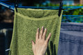 Dirty hand touching clean laundry a covered in muck is about to touch some hanging on a clothes line Royalty Free Stock Images