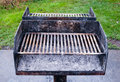 Dirty metal barbecue grill with ashes old grills on cement base and against grass remains of gray Royalty Free Stock Photos