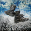 Dirty military boots over grunge background Royalty Free Stock Photo