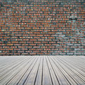 Dirty old bricks wall with wooden floor background Royalty Free Stock Image