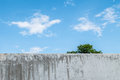 Dirty and old concrete wall with beautiful blue sky at the midday background Stock Images