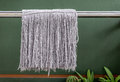 Dirty and old mops hanging on washing line Royalty Free Stock Photo