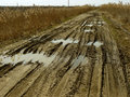 Dirty rural road with deep tire tracks Stock Photo