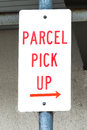 Dirty sign stating parcel pick up with right arrow red and white on post pointing Royalty Free Stock Images