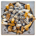 Dirty steel ashtray full of old cigarette and cigar butts Stock Photos