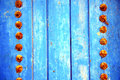 Dirty stripped paint in the blue wood door and rusty nail Stock Images