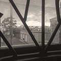 Dirty window security bars duotone looking through and over garages and cloudy sky copyspace Royalty Free Stock Photo