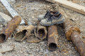 Dirty work boots on old pipes at construction site Stock Photos