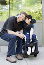 Disabled boy hugging father while waiting at hospital six year old in wheelchair Royalty Free Stock Images