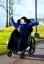 Disabled boy in wheelchair enjoying day at park arms raised happiness Stock Photography