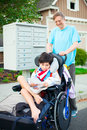 Disabled boy in wheelchair getting mail from mailbox with father Royalty Free Stock Photo