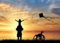 Disabled child on shoulders of dad playing with kite and wheelchair near sea sunset Royalty Free Stock Photo